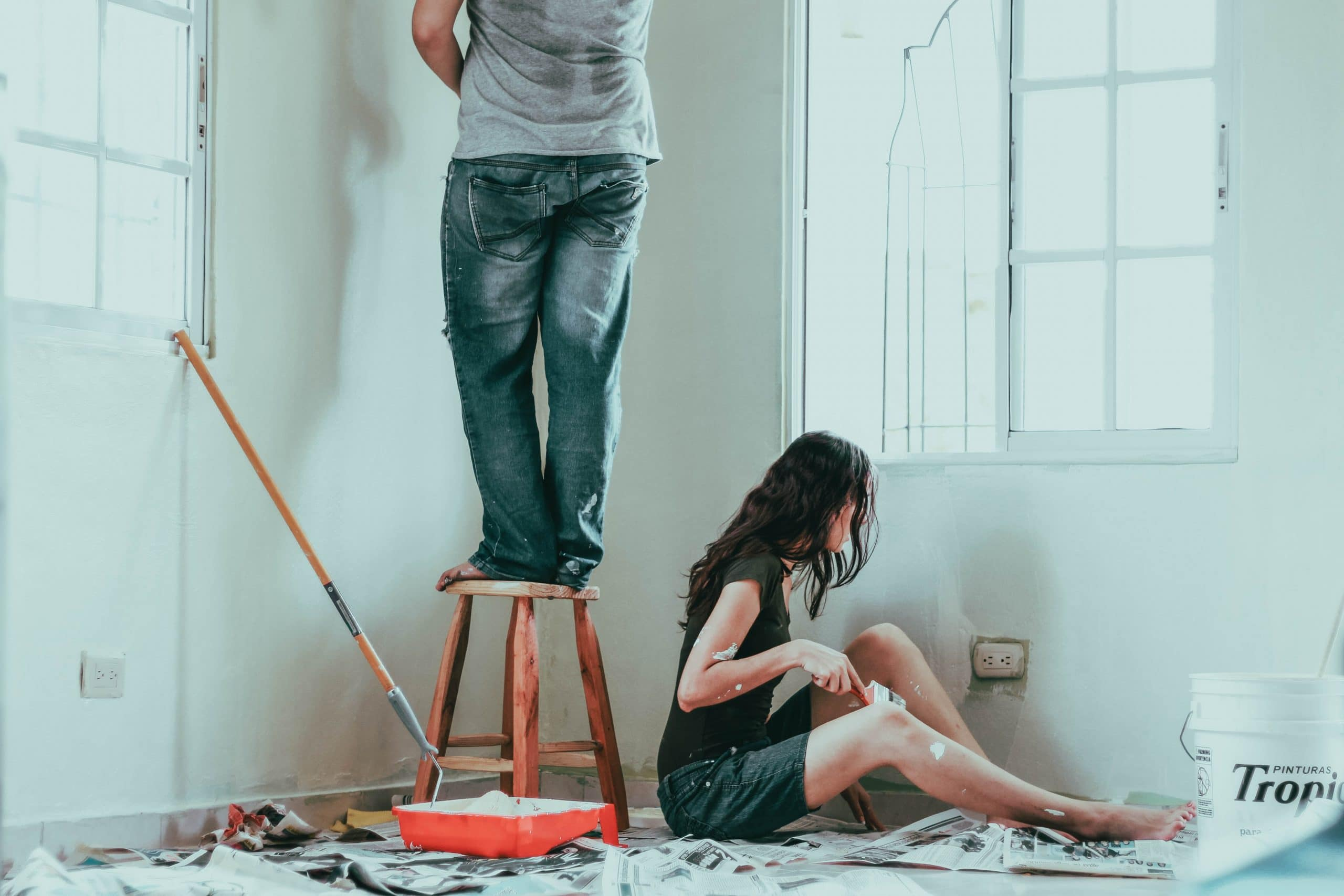 a couple painting the walls of their home