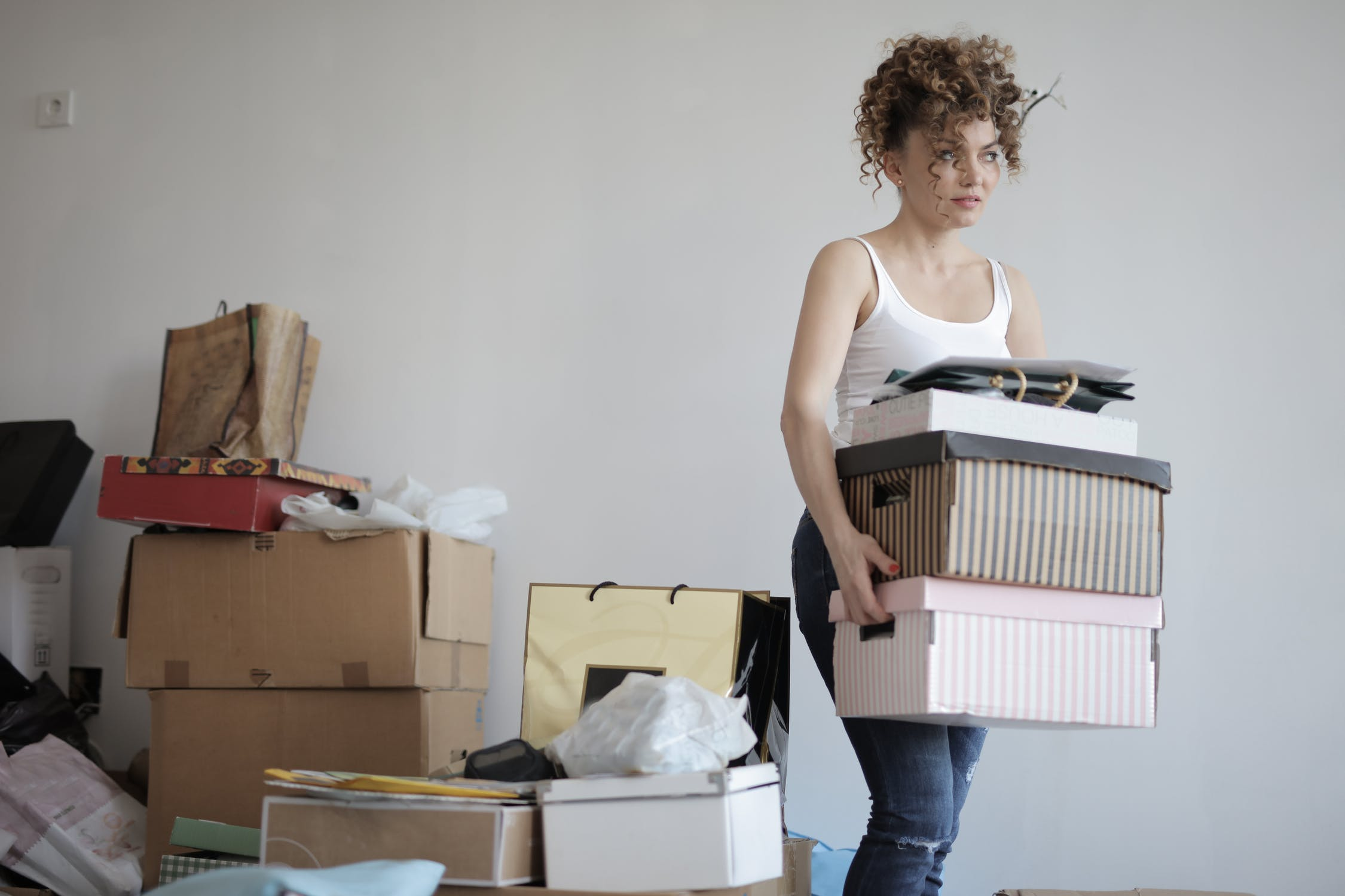 Woman holding boxes with a pile of things behind her